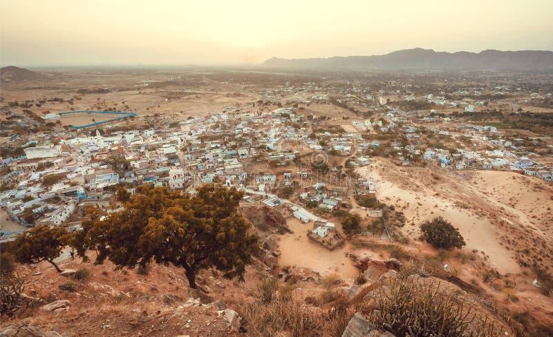 Bäume und Hügel um indische Stadt Berge und viele Gebäude von Pushkar am Abend, Rajasthan-Staat, Indien lizenzfreies stockfoto