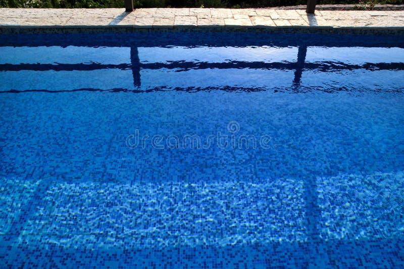 Błękit rozdzierał wodę w basenie w tropikalnym kurorcie z krawędzią bruk Część basenu dna tło zdjęcia royalty free