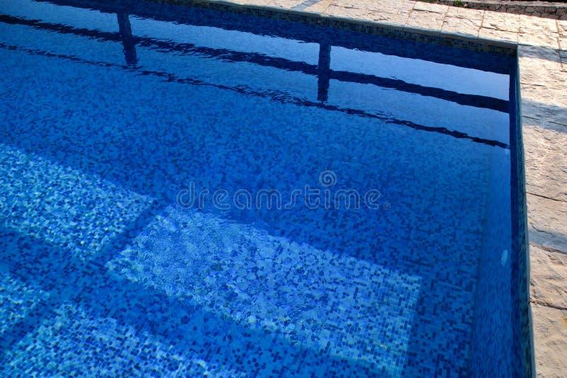 Błękit rozdzierał wodę w basenie w tropikalnym kurorcie z krawędzią bruk Część basenu dna tło zdjęcia stock