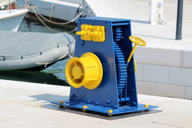 Błękita i żółtego przywrócić rocznika obsady żelaza pulley retro koło wspinający się na tradycyjnym kamieniu tafluje molo używać  obraz royalty free