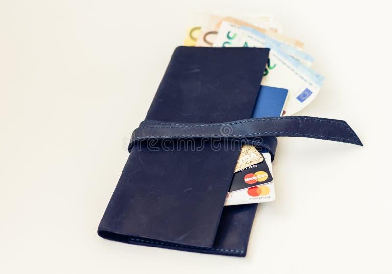 Błękitna rzemienna kiesa odizolowywająca na białym tle z euro, paszportem i kartami kredytowymi wtyka z go, fotografia royalty free