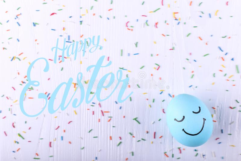 Błękitny jajko z malującymi uśmiechami Szczęśliwy Wielkanocny pojęcie kartki z pozdrowieniami projekt obraz stock