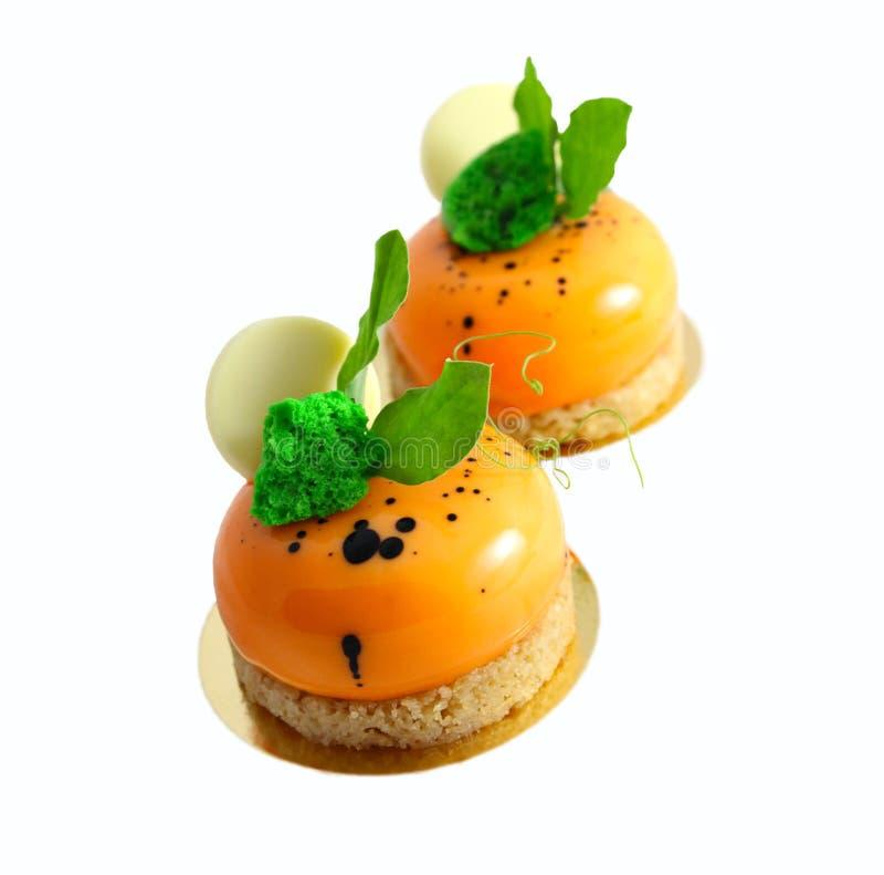 Błyszczący jaskrawi pomarańczowi marchwiani torty z czarnymi kropkami, grochów liśćmi i białą czekoladą na białym tle, zdjęcia royalty free