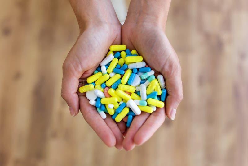 Båda händer av innehavgruppen för ung kvinna av preventivpillerar Överdos- eller missbrukbegrepp royaltyfria foton