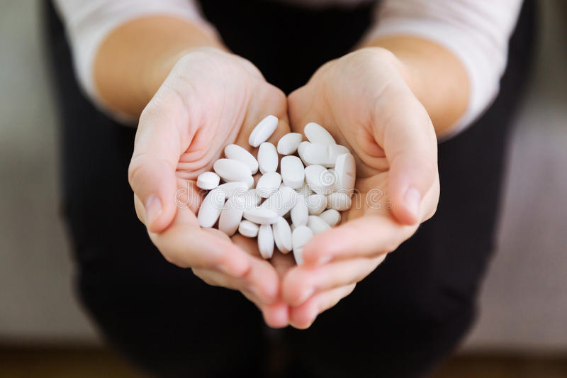 Båda händer som rymmer gruppen av preventivpillerar Överdos- eller missbrukbegrepp arkivfoto