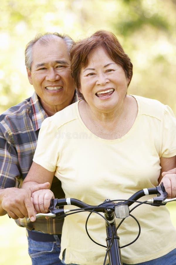 Båda höga asiatiska par sammanträde på en cykel parkerar in arkivfoto