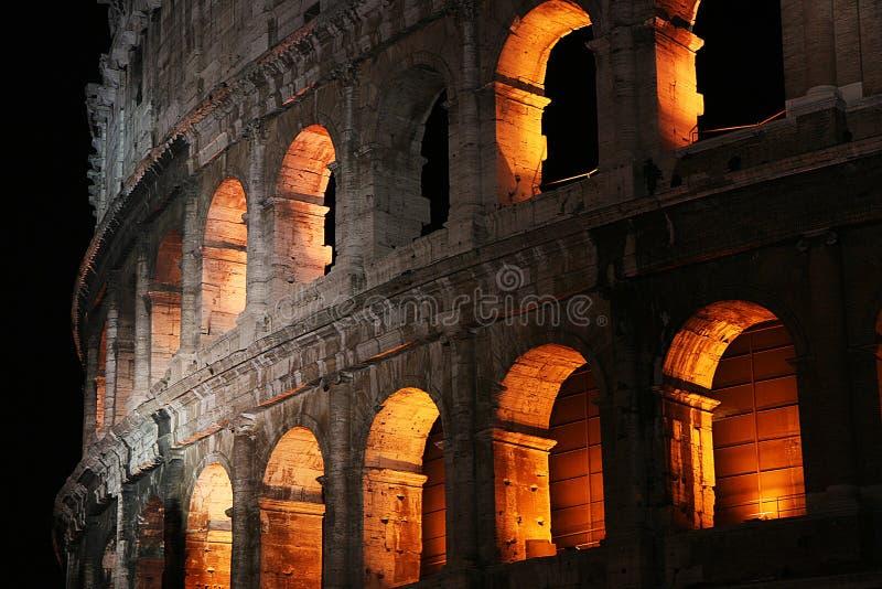 Bågar av Colosseumen på natten arkivfoto