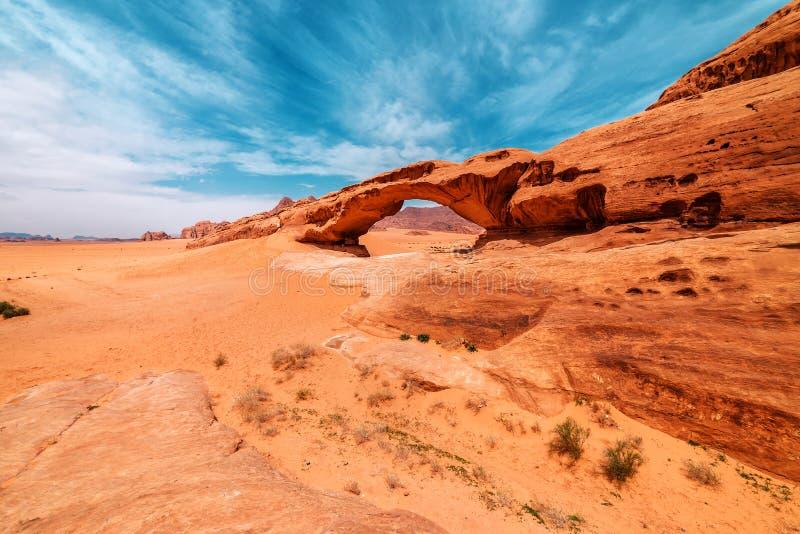 Bågbildande på ett stort vaggar i den Wadi Rum öknen royaltyfri bild
