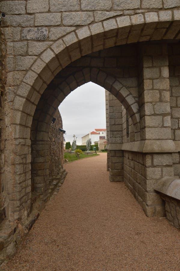Båge av halv punkt i trädgården med bakgrund för tre änglar av den biskops- slotten i Astorga Arkitektur historia, Camino De royaltyfri bild