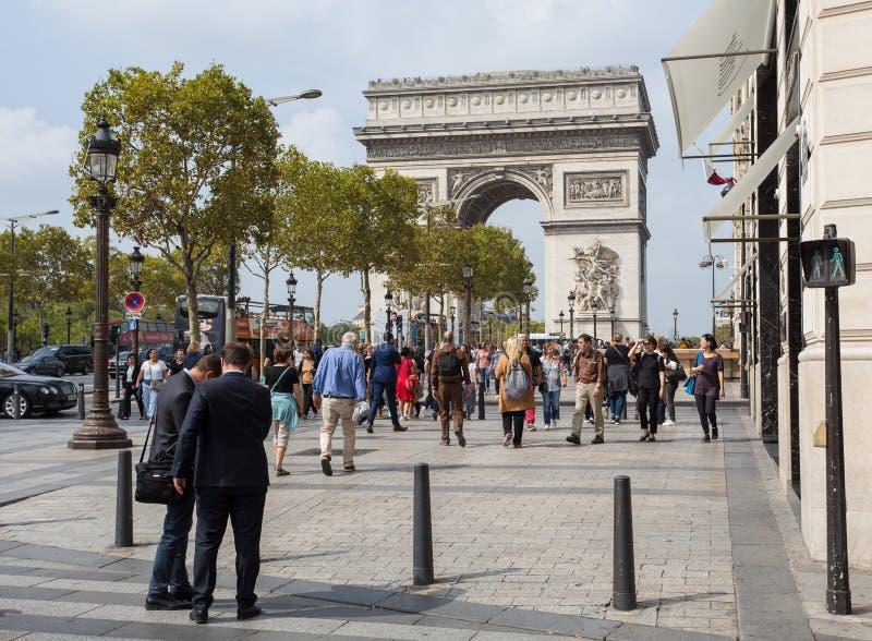 Båge av Triumph från avenydesen Champs-Elysees Gatan är alltid full av liv av turister och affärsfolk royaltyfri bild