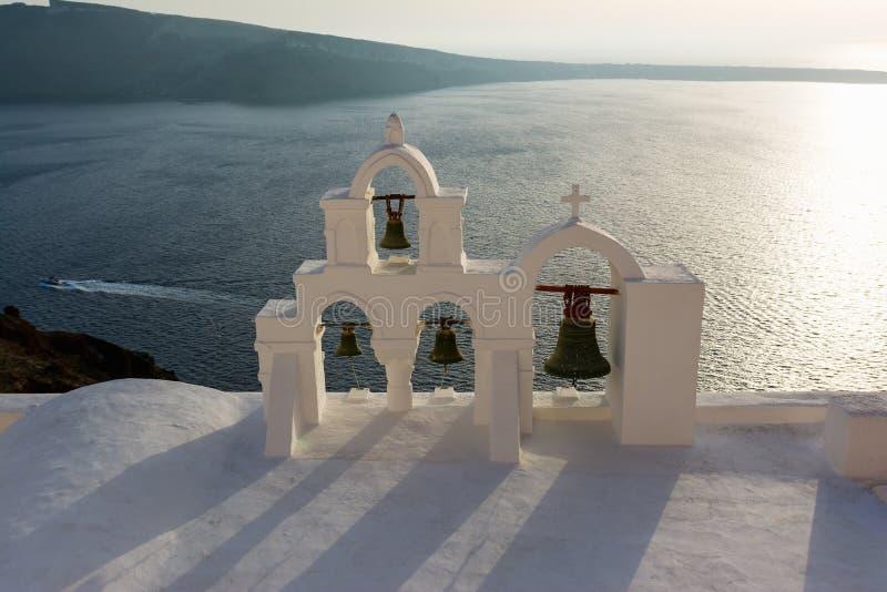 Båge med korset och klockor av den traditionella grekiska vita kyrkan i den Oia byn, Santorini ö, Grekland fotografering för bildbyråer