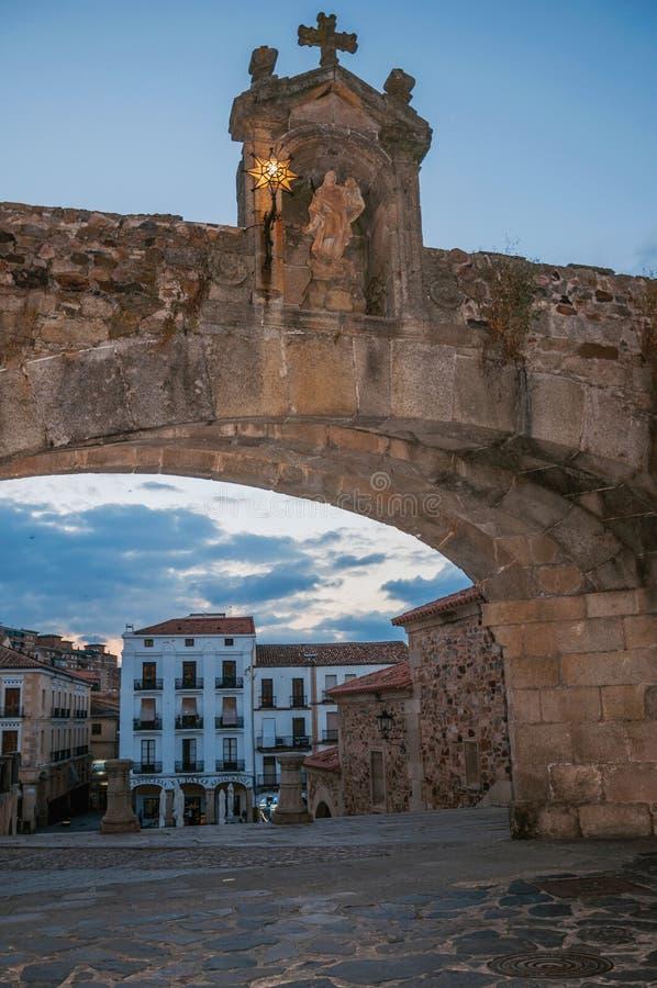 Bågenyckel med skulptur av våra dam och gamla byggnader på skymning i Caceres arkivbilder