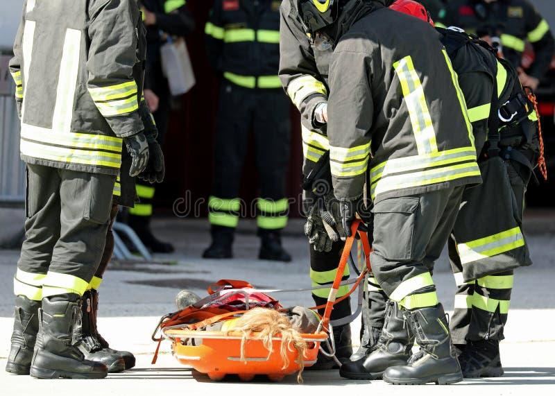 båren med sårat och brandmän, som sparade, sårar arkivbilder