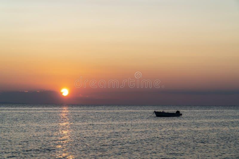 Båt mitt i havet under solnedgången arkivfoto