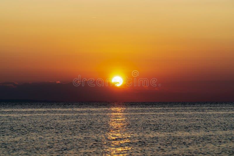Båt mitt i havet under solnedgången arkivfoton