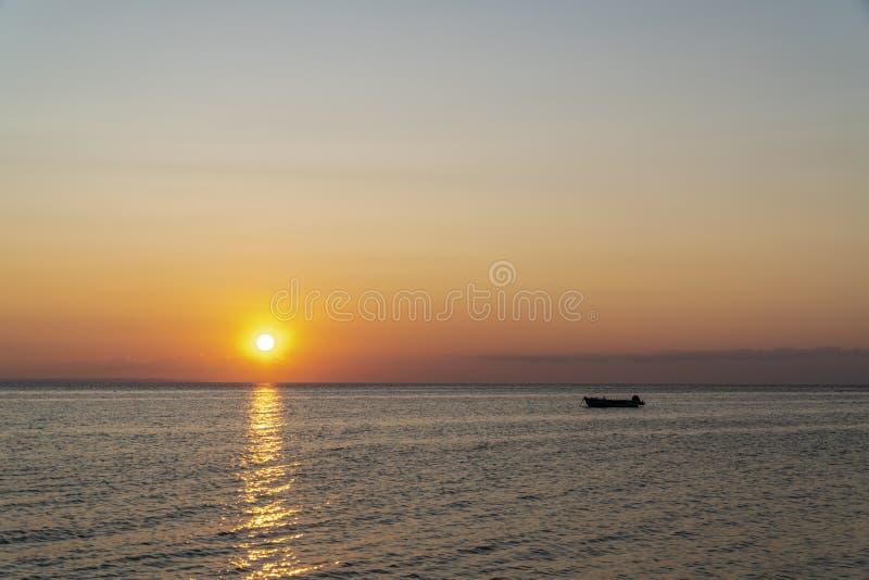 Båt mitt i havet under solnedgången royaltyfri foto