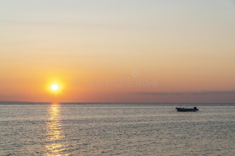 Båt mitt i havet under solnedgången royaltyfri bild