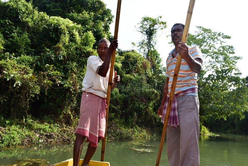 Båtuthyrare kör fartyget till och med Buxa Tiger Reserve i västra Bengal, Indien En fartygritt till och med djungeln arkivfoton