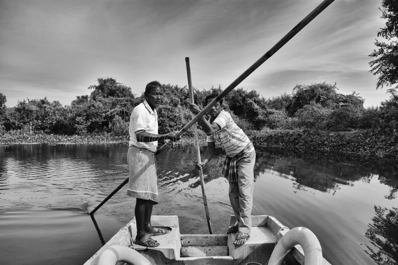 Båtuthyrare kör fartyget till och med Buxa Tiger Reserve i västra Bengal, Indien En fartygritt till och med djungeln arkivbilder