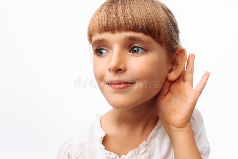 Bébé écoutant ou écoutant clandestinement, dans le studio sur le fond blanc, fin  photos stock