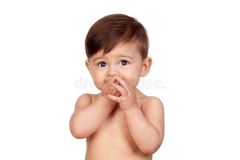 Bébé adorable avec les mains dans sa bouche