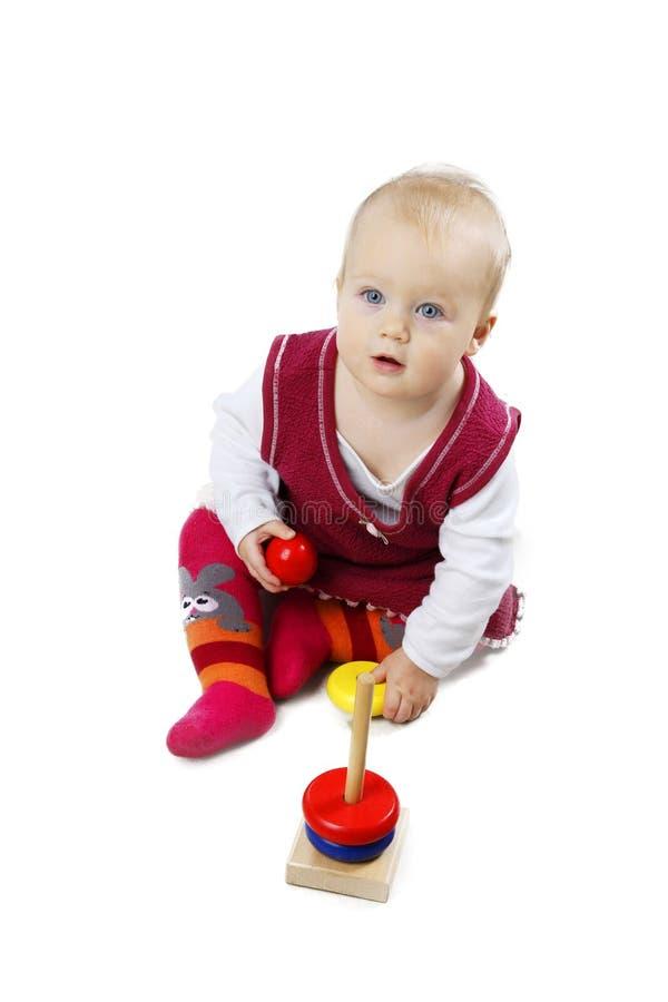 Bébé adorable dans des vêtements rouges jouant avec quelques jouets image libre de droits