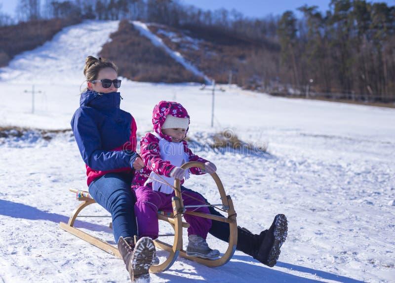 Bébé adorable dans une neige blanche dans l'emplacement chaud de costume dans la neige image stock