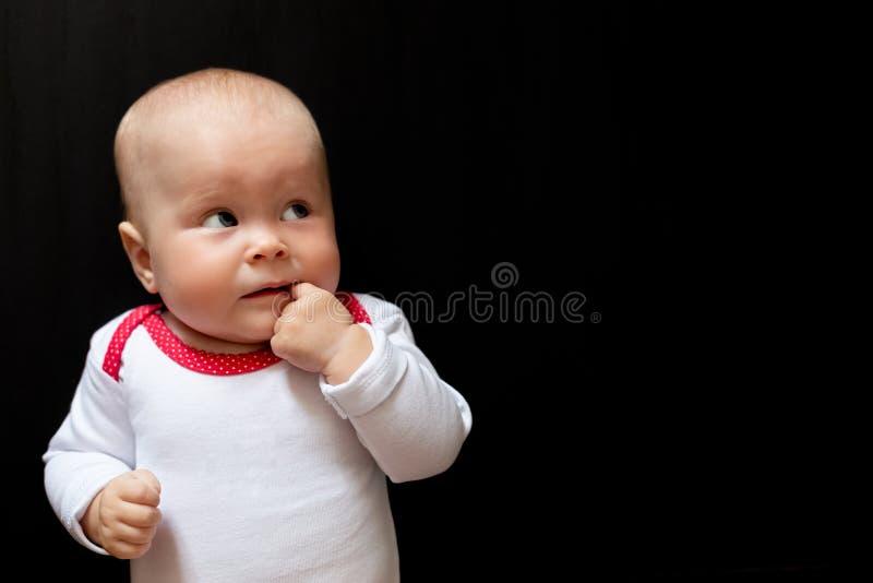 Bébé adorable et mignon avec des yeux bleus et avec son doigt la bouche et en recherchant Nourrisson sur le noir photos stock
