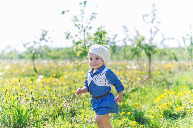 Bébé adorable marchant dans l'herbe verte dans la pelouse, jouer et rire de forêt image stock