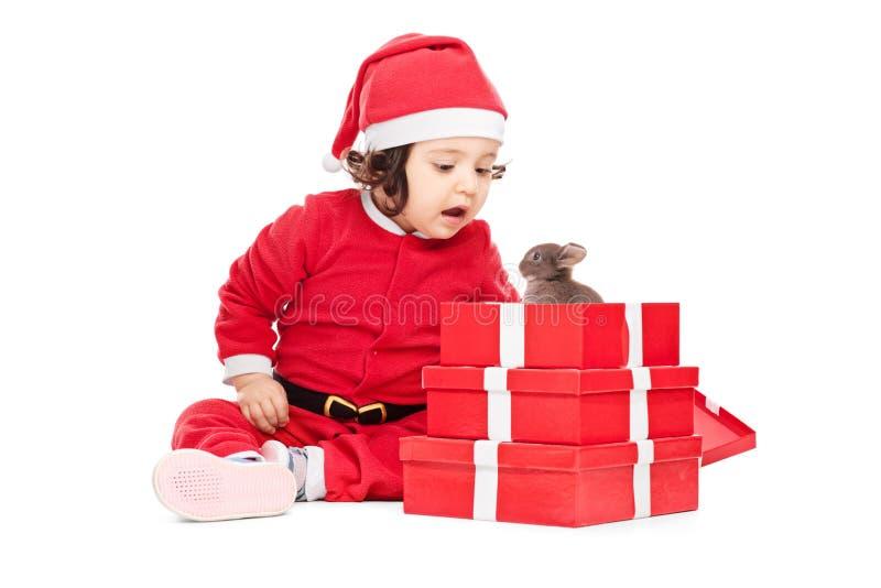Bébé adorable ouvrant les cadeaux de Noël photographie stock