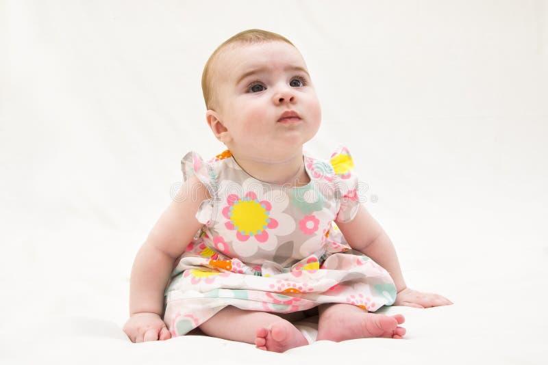 Bébé adorable s'asseyant sur le plancher, photo libre de droits