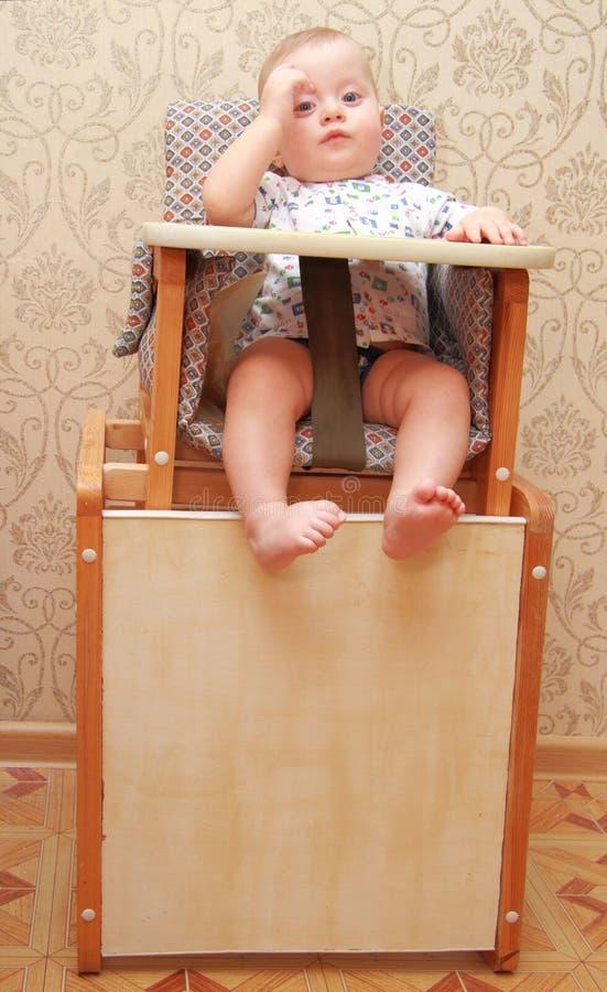 Bébé adorable sur le highchair, à la maison image stock