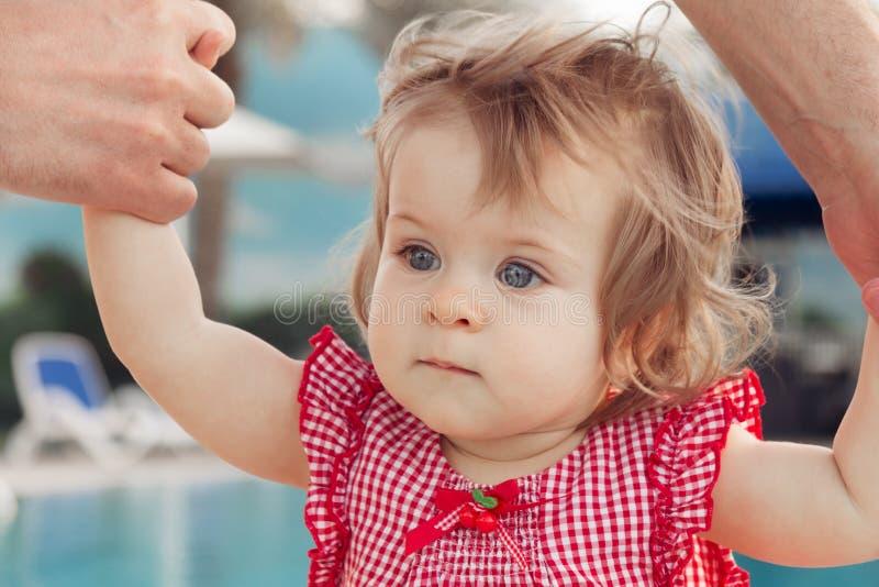 Bébé adorable tenant les mains du père tout en apprenant à marcher dehors Fond de piscine Chéri recherchant image stock