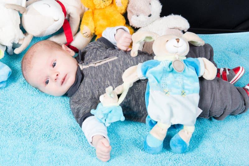 Bébé allongé sur la couette bleue douce Concept d'innocence et d'enfance Infant aux yeux bleus et sourire paisible parmi les ours photos stock