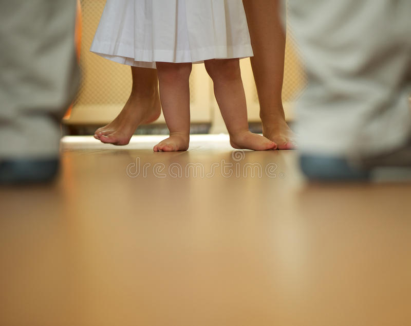 Bébé apprenant à marcher avec l'aide de la mère et du père images libres de droits