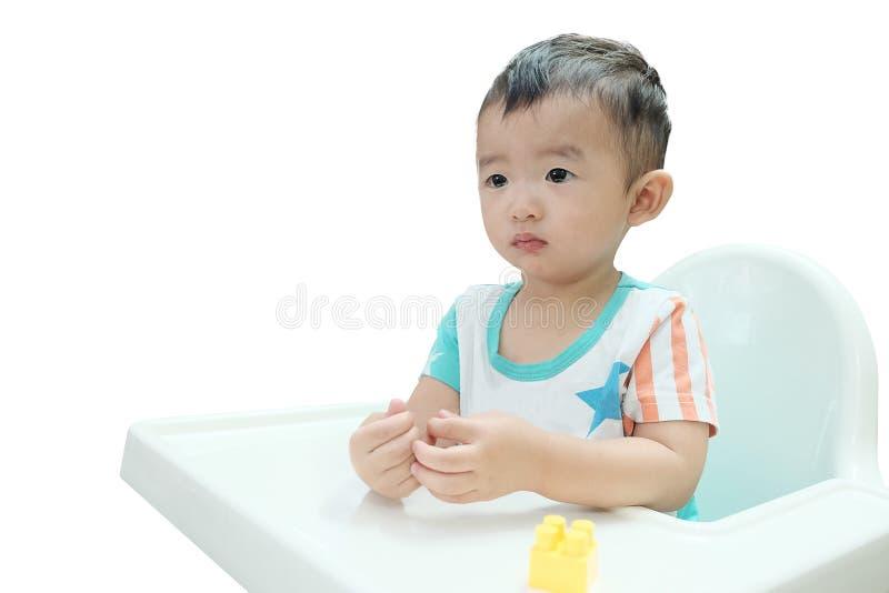 Bébé asiatique affamé dans le highchair Nourriture de attente d'enfant, isolat photos stock