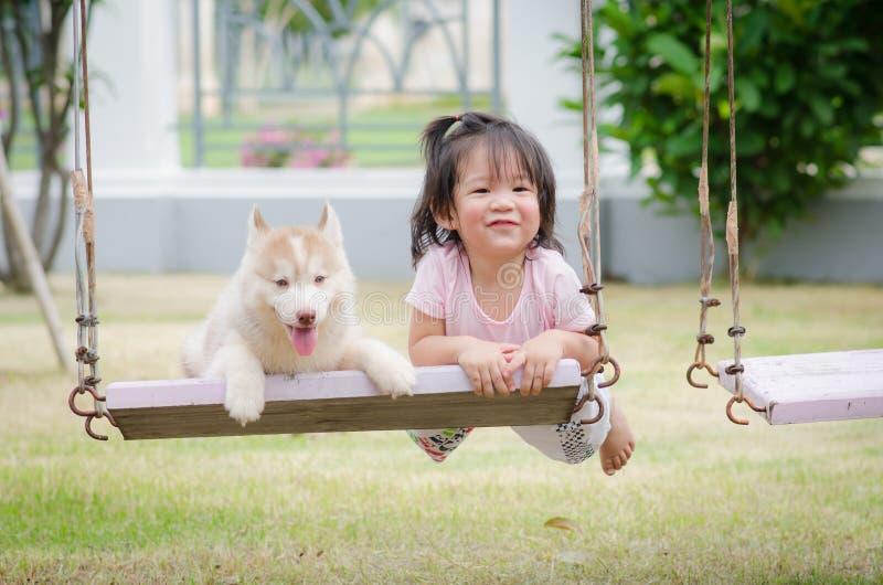 Bébé asiatique de bébé sur l'oscillation avec le chiot photo stock