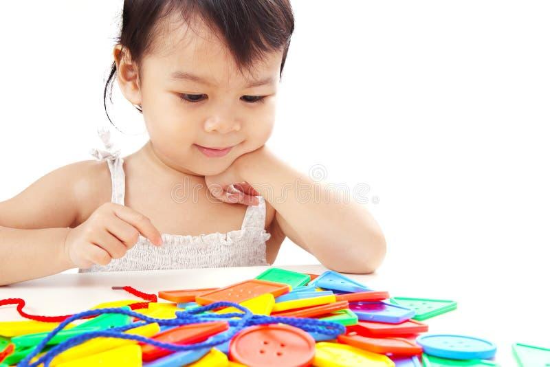 Bébé asiatique de plan rapproché jouant filetant la ligne Toy Isola de boutons photo stock
