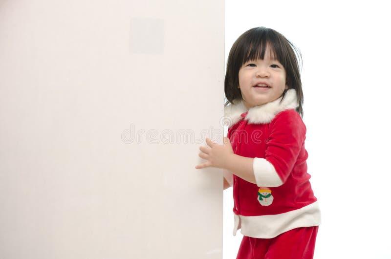 Bébé asiatique mignon dans le costume de Santa avec le tableau blanc images stock