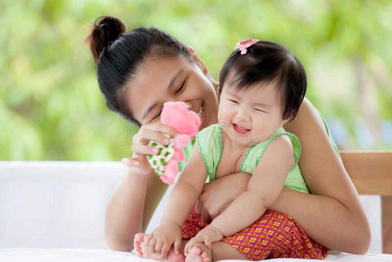 Bébé asiatique mignon souriant et jouant avec sa mère photographie stock libre de droits