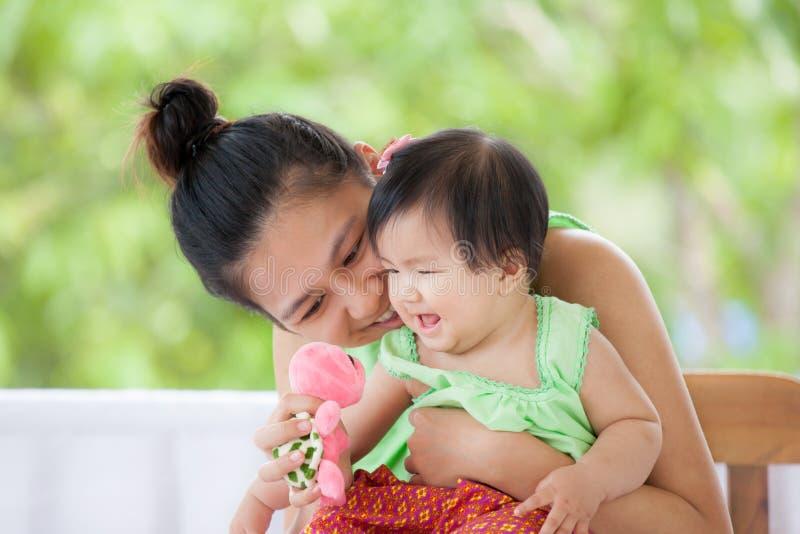 Bébé asiatique mignon souriant et jouant avec sa mère image libre de droits