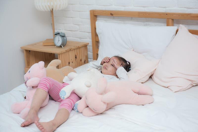 Bébé asiatique se réveillant dans le lit avec la poupée malheureuse images libres de droits