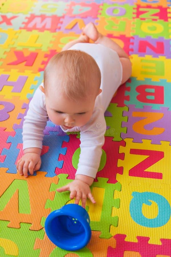 Bébé atteignant pour la tasse sur le tapis d'alphabet photos libres de droits
