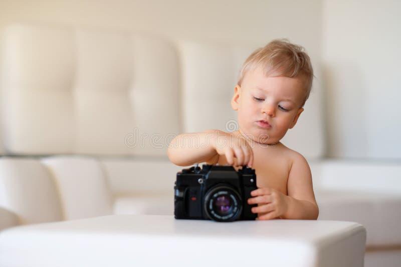 Bébé avec des œil bleu Enfant d'enfant en bas âge explorant le vieil appareil-photo photographie stock libre de droits