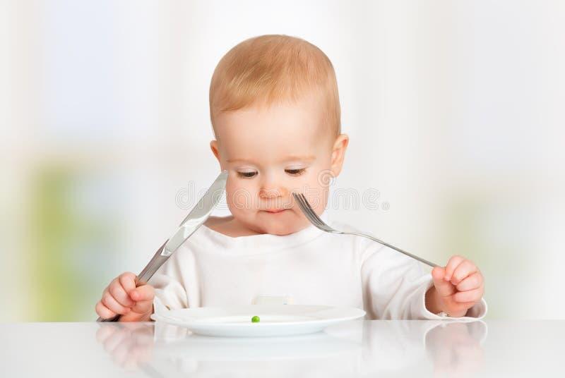Bébé avec la consommation de fourchette et de couteau, regardant le plat avec un p photographie stock