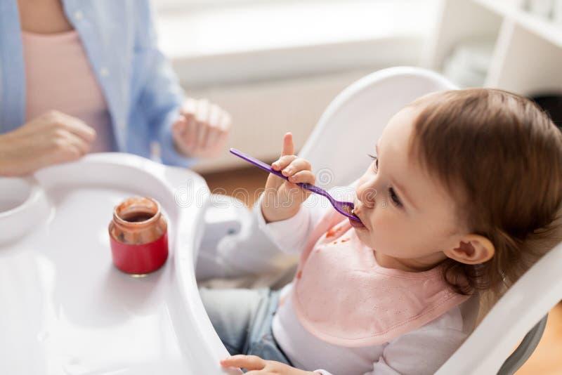Bébé avec la cuillère mangeant de la purée du pot à la maison photographie stock libre de droits