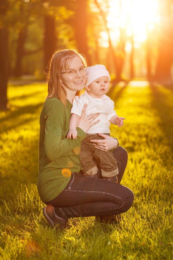 Bébé avec la mère en parc dans les rayons du coucher du soleil Enfant en bas âge avec la maman sur la nature dehors Contre-jour S photo libre de droits