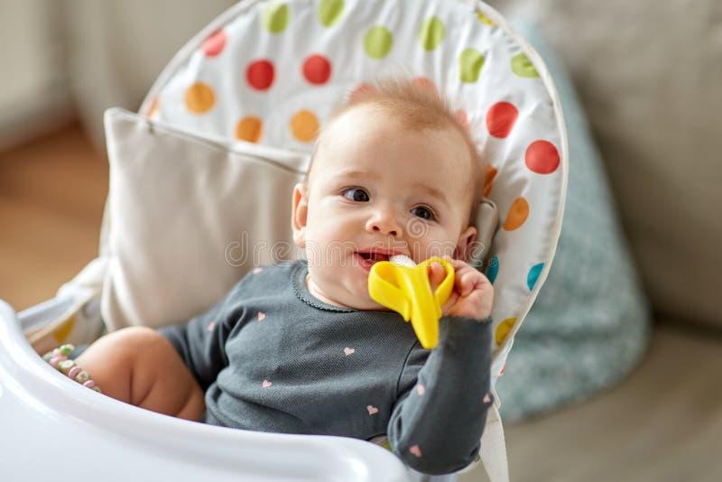 Bébé avec le jouet de teether dans le highchair à la maison photo stock