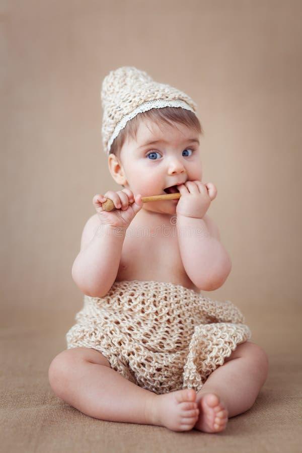 Bébé avec une cuillère tricotée de chapeau et de miel tout en regardant dans la caméra images stock