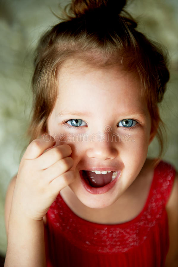 Bébé avec une touffe sur la tête, avec des yeux bleus et le sourire espiègle images stock